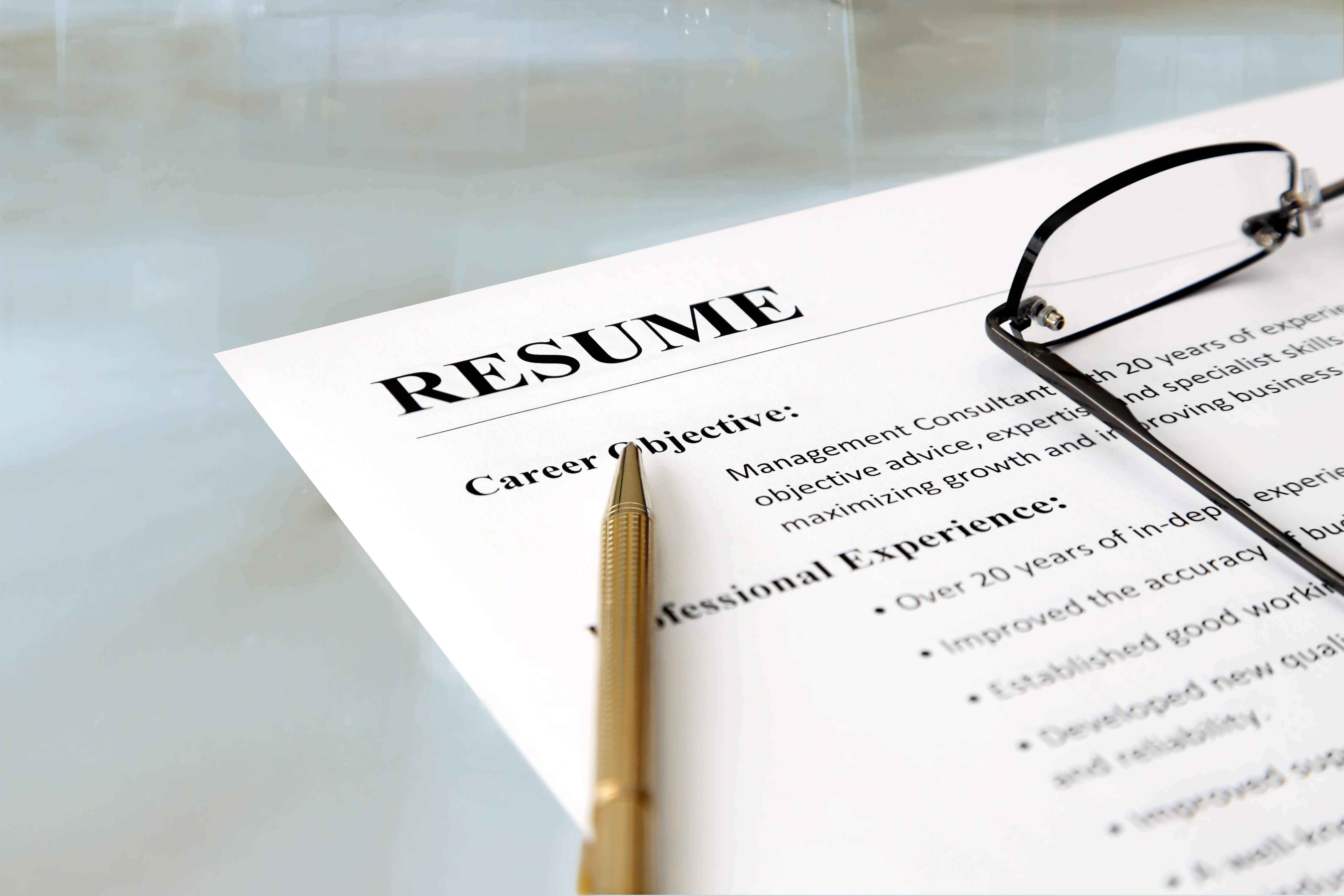 closeup of resume with pen and glasses on the table shs